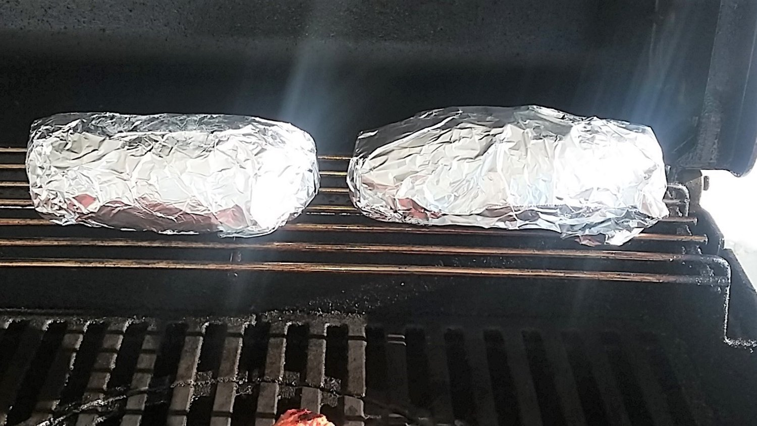 Whole potatoes wrapped in foil on gas grill