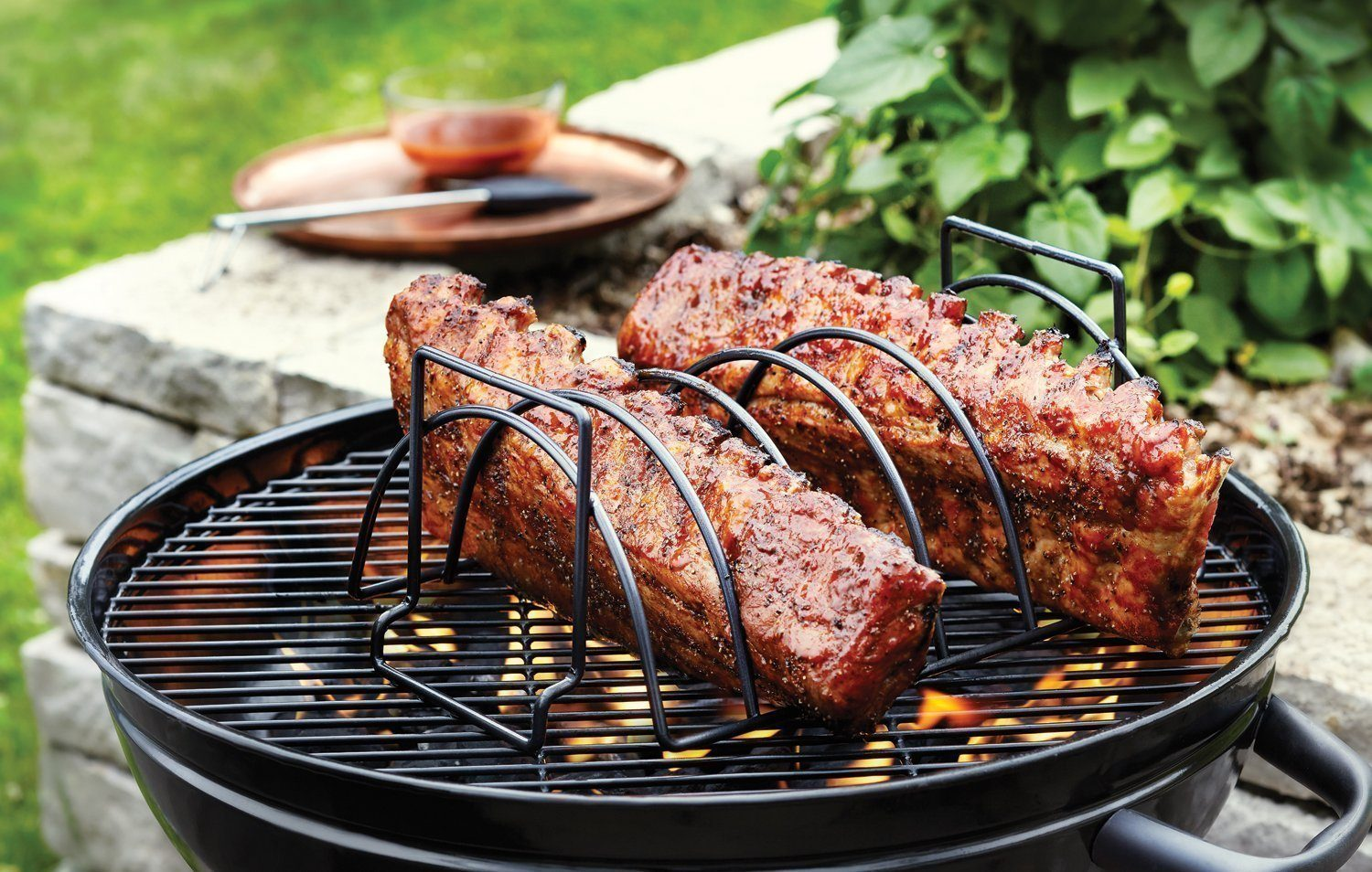 Rib rack on charcoal grill with ribs