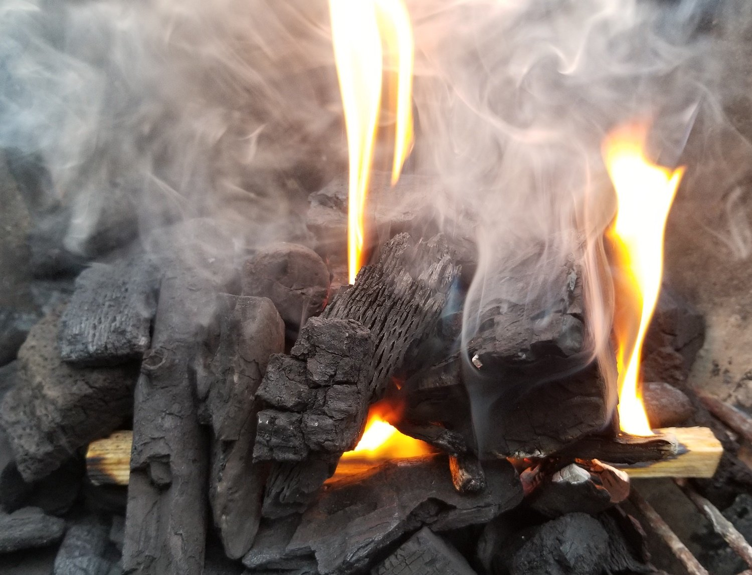 Bettwrwood lump charcoal being lit with fatwood firestarter